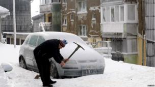 A man smashes ice with a pickaxe next to car covered with ice