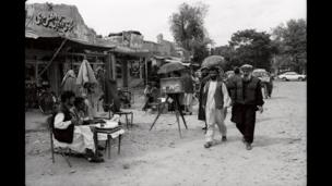Scribes sitting alongside a box camera photographer. Other box camera photographers work on the street. Charah-e-Sedarat, Kabul, May 4th 2002.