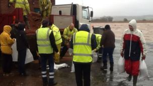 Residents being handed sandbags in Topsham, near Exeter, in Devon