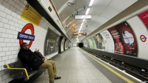 A passenger waits on an empty platform at Oxford Circus Underground station