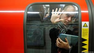 A passenger is squeezed up against a door at Oxford Circus underground station in London
