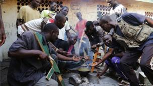 Army recruits demanding food from a small bowl at Bokassa's old palace - Central African Republic, February 2014