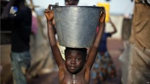 A child carrying a bucket of water on her head, Bangui airport, CAR - Sunday 2 February 2014
