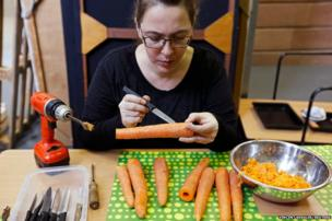A member of the Vegetable Orchestra, makes a musical instrument from a carrot