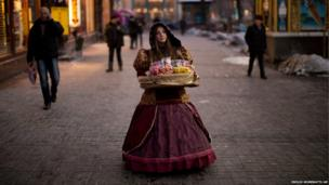 A woman sells sweets in a street heading to Kiev's Independence Square