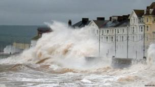 Huge waves crash against houses on the seafront in Exmouth, Devon. Photo: Stuart Bell