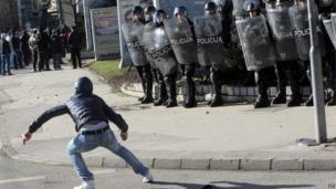 Protester in front of riot police in Sarajevo (7 February 2014)
