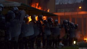 Riot police stand in front of a burning government building. Photo: Sindre Langmoen
