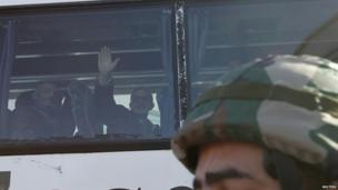 Man waves from a bus transporting residents from a besieged area of Homs 7 February 2014