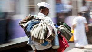 A Dabbawala carrying bags of tiffin tins on his shoulder