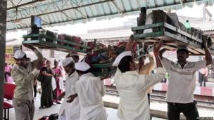 Dabbawalas carrying crates of tiffin tins on their heads.