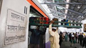 Dabbawala loading tray onto a train car
