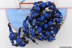 Sweden's players celebrate after winning the Women's Ice Hockey Group B match Germany vs Sweden at the Shayba Arena during the Sochi Winter Olympics on February 11, 2014.