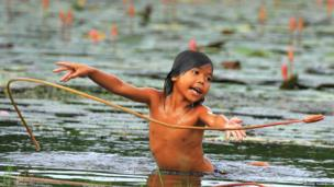 A girl in a pond with flowers