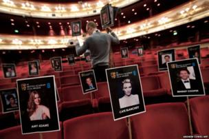 Staff members of the British Academy of Film and Television Arts (Bafta) place photographs of Bafta awards attendees on seats at the Royal Opera House in London