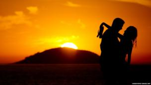 A couple is seen at sunrise on Copacabana beach on the eve of Valentines Day in Rio de Janeiro.