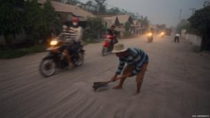 Man clears a road covered in ash