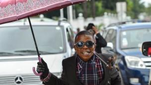 A sapeur in a suit with a pipe, round sunglasses and an umbrella in Kinshasa, DR Congo - Monday 10 February 2014
