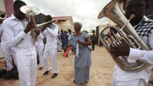 A woman dancing to music played on brass instruments in the royal court in Abengourou, Ivory Coast - Friday 7 February 2014