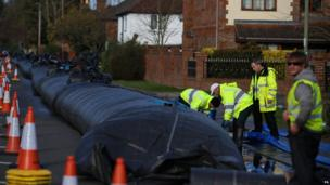 Workers install an aqua dam