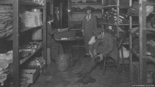 A female orderly kitting out two patients in the clothing store at Endell Street Military Hospital during World War One