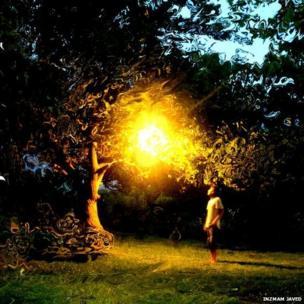 Image of man standing under light in dark garden