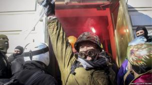 Protesters gather by the entrance as they attack an office of the pro-presidential Party of the Regions in Kiev