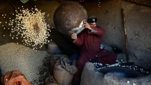 An Afghan popcorn vendor works inside his shop in Kabul on February 18, 2014