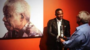 The Queen's Baton held by Luvuyo Mandela, great-grandson of Nelson Mandela, at the Nelson Mandela Foundation's Centre of Memory, in Johannesburg.