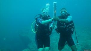 The baton goes underwater in the Seychelles held by British High Commissioner Lindsay Skoll.