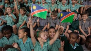 Children from Pioneers Park Primary School in Windhoek, Namibia cheer wildly for the arrival of the Queen's baton.