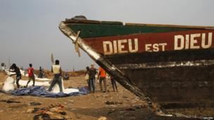 """A boat with the words """"Dieu est Dieu"""" painted on its side, Bangui, CAR"""
