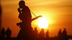 A Sudan Sudanese rebel pictured as the sun rises or sets in Upper Nile, South Sudan - Friday 14 February 2014
