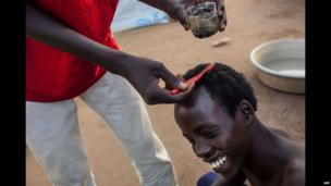 A teenager gets his hair dyed in a UN base, Juba, South Sudan - Wednesday 19 February 2014