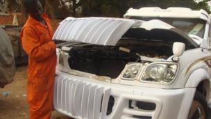 Godfrey Namunye opening the bonnet of a car at his workshop in Kampala, Uganda