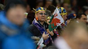 A French fan waves a Welsh flag as his countrymen fall short on the Millennium Stadium pitch