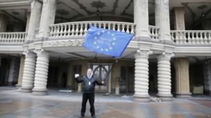 Protester waves EU flag at presidential residence outside Kiev, Ukraine (22 Feb 2014)