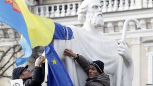Protesters tie an EU flag to a statue
