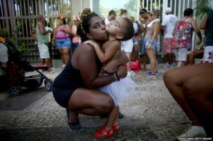 """Janina Gama kisses her daughter Isadora during a """"bloco"""" street party during pre-Carnival festivities in Rio de Janeiro, Brazil."""
