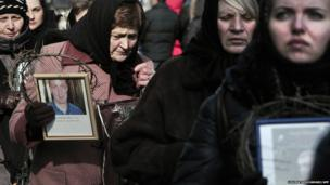 Women hold pictures of the killed protesters while walking in procession in central Kiev