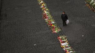 A man walks alongside a memorial for the people killed in clashes with police in Kiev's Independence Square