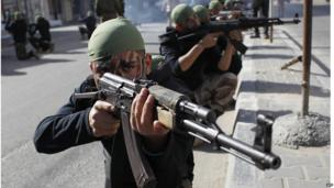 Palestinian students take part in a military march organised by Hamas in a street in Rafah on 27 February