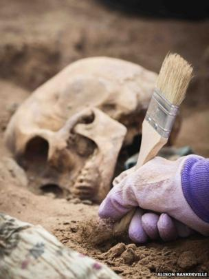 The team use paintbrushes to dust carefully around the bones as there may loose teeth and smaller bones that have fallen away in the grave