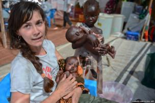 A Medecins Sans Frontieres (MSF) worker holds a South Sudanese baby while two little girls wait for treatment at the MSF hospital in Juba
