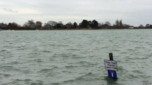 High tide floods the lower road and several car parking spaces in Bosham, West Sussex.