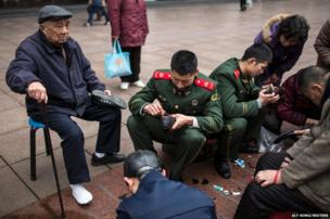 Members of the Chinese People's Armed Police mend shoes