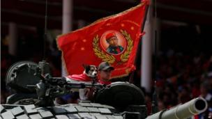 A dog wearing a cape stands on a tank flying a flag decorated with an image of Venezuela's former President Hugo Chavez at a military parade commemorating the anniversary of Chavez's death in Caracas on 5 March, 2014