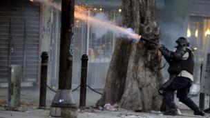A police officer shoots tear gas at opposition activists during a protest against the government of Venezuelan President Nicolas Maduro on 5 March, 2014