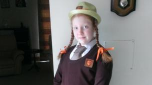 Ellen in school uniform with hat and pigtails