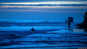 A surfer makes his way to shore long after sunset in Cardiff, California
